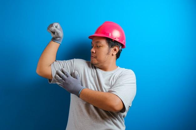 Portret van een grappige dikke aziatische man met een rode helm die trots glimlacht terwijl hij dubbele biceps laat zien, kracht boven vertrouwenconcept