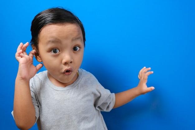 Portret van een grappige jonge aziatische jongen die naar de camera kijkt met grote ogen die zijn mond bedekken, een geschokte, verbaasde uitdrukking tegen een blauwe achtergrond
