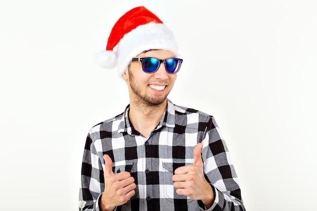 Portret van een grappige jonge man in kerstman hoed en baard op witte ruimte. kerstmis.
