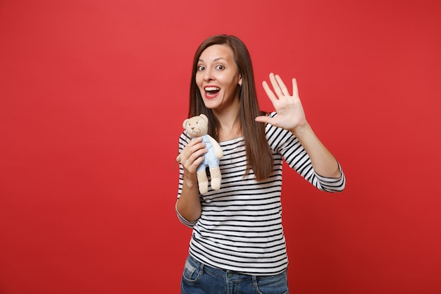 Portret van een grappige jonge vrouw in gestreepte kleding met teddybeer knuffel met palm, zwaaiende hand