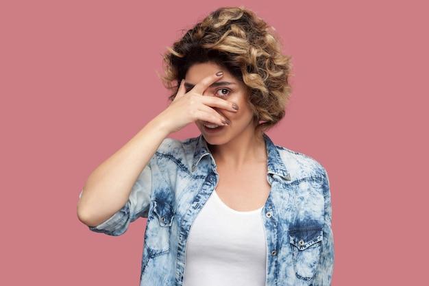 Portret van een grappige jonge vrouw met krullend kapsel in een casual blauw shirt dat staat, haar ogen bedekt en door de vingers kijkt. spion of verlegen concept. indoor studio opname, geïsoleerd op roze achtergrond.