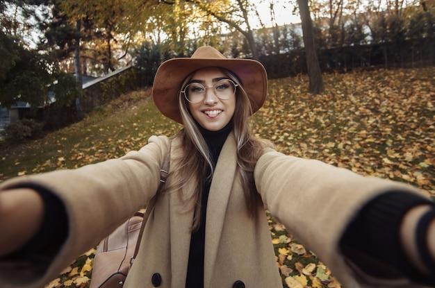 Portret van een grappige jonge vrouw op de achtergrond van gevallen bladeren in het park. herfst tijd