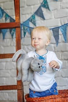 Portret van een grappige kleine babyjongen met een stuk speelgoed katje