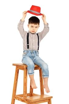 Portret van een grappige kleine jongen, zittend op een hoge kruk in een rode hoed op wit wordt geïsoleerd