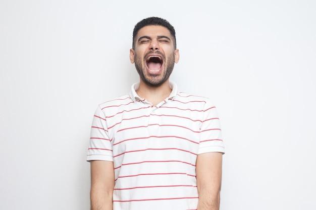 Portret van een grappige, knappe, bebaarde jongeman in een gestreept t-shirt met gesloten ogen en lachend. indoor studio opname, geïsoleerd op een witte achtergrond.