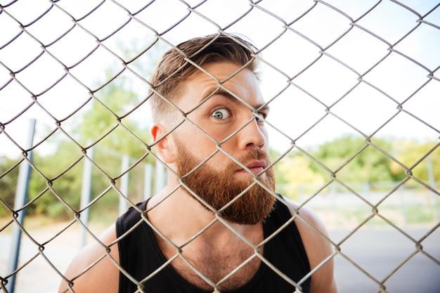 Portret van een grappige man met een baard die buiten door het metalen hek kijkt