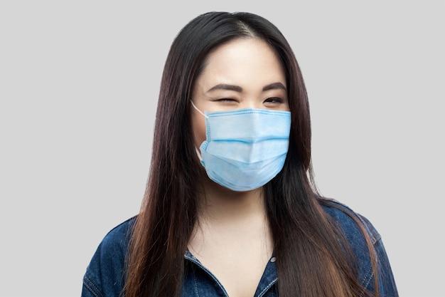 Portret van een grappige, mooie brunette aziatische jonge vrouw met een chirurgisch medisch masker in een blauwe spijkerjas die met een glimlach knipoogt en naar de camera kijkt. studio-opname, geïsoleerd op lichtgrijze achtergrond