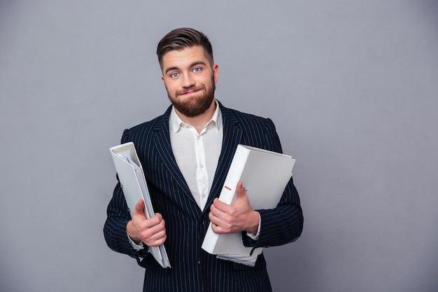 Portret van een grappige omslagen van de zakenmanholding over grijze muur