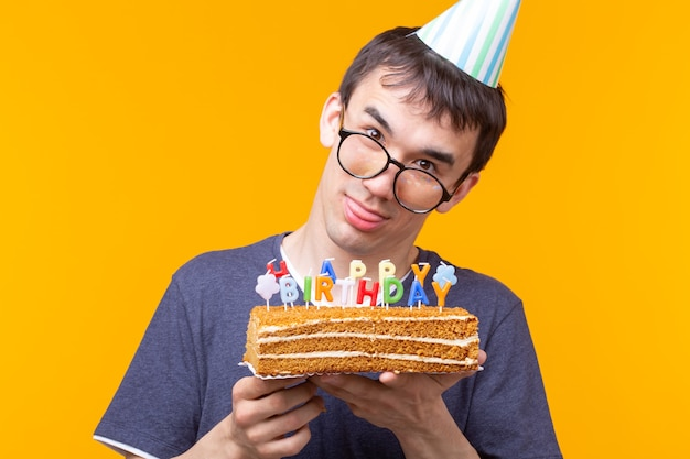 Portret van een grappige positieve man met een papieren pet en een bril met een zelfgemaakte felicitatiecake