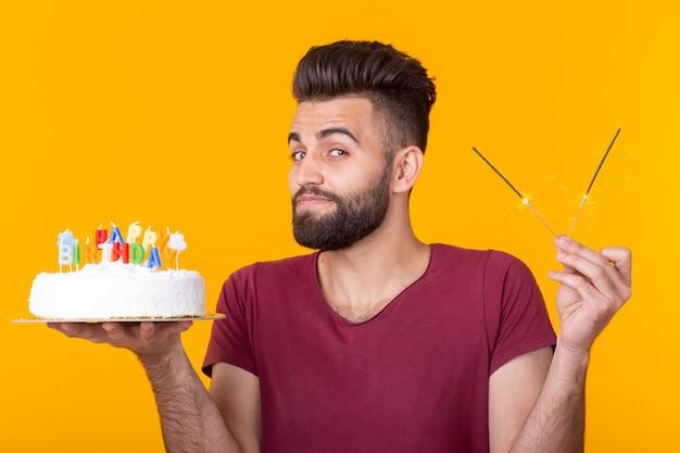 Portret van een grappige positieve man met een zelfgemaakte cake met felicitatie in zijn handen op een gele achtergrond. concept en plezier en feest.