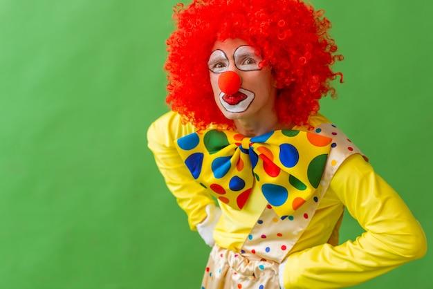 Portret van een grappige speelse clown in rode pruik.
