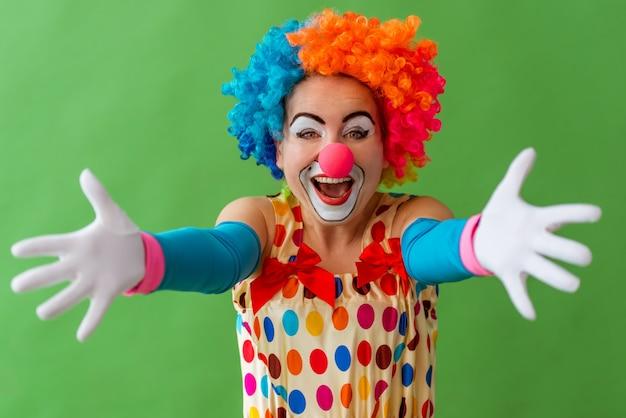 Portret van een grappige speelse vrouwelijke clown in kleurrijke pruik.