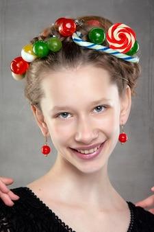 Portret van een grappige tiener met een krans van snoep op haar hoofd.