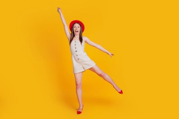 Portret van een grappige, zorgeloze, schattige dame veel plezier met het opsteken van de hand op gele achtergrond