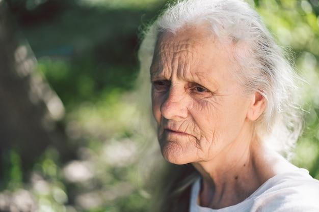 Portret van een grijsharige volwassen grootmoeder tegen de achtergrond van de natuur
