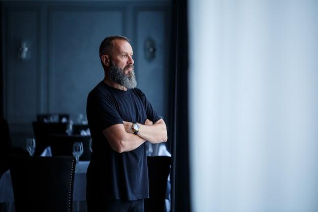 Portret van een grijsharige volwassen succesvolle man met een serieus gezicht in een zwart t-shirt