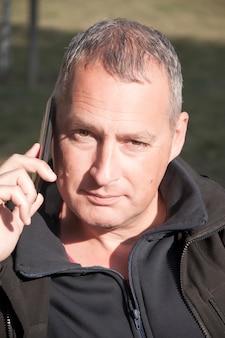 Portret van een grijze haren man in een gesprek via de mobiele telefoon.