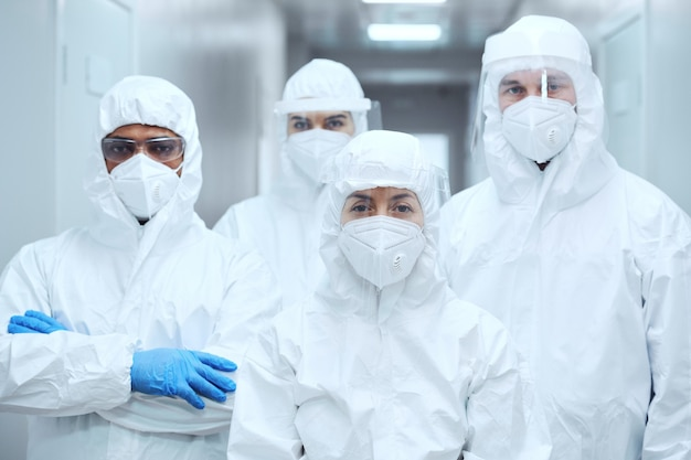 Portret van een groep artsen in uniform die naar de camera kijken terwijl ze in het ziekenhuis werken tijdens een pandemie