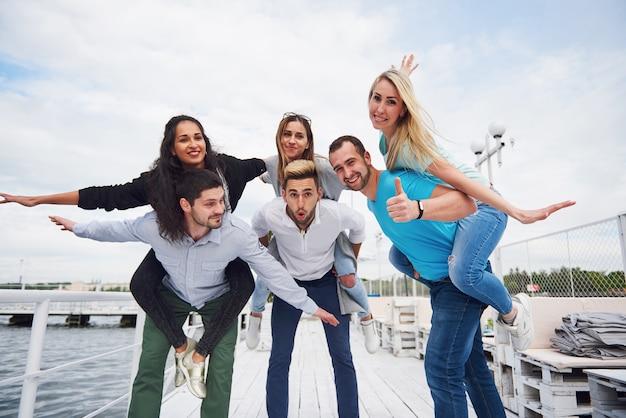 Portret van een groep jonge mensen zittend op de rand van de pier, buiten in de natuur. vrienden die genieten van een spel op het meer.