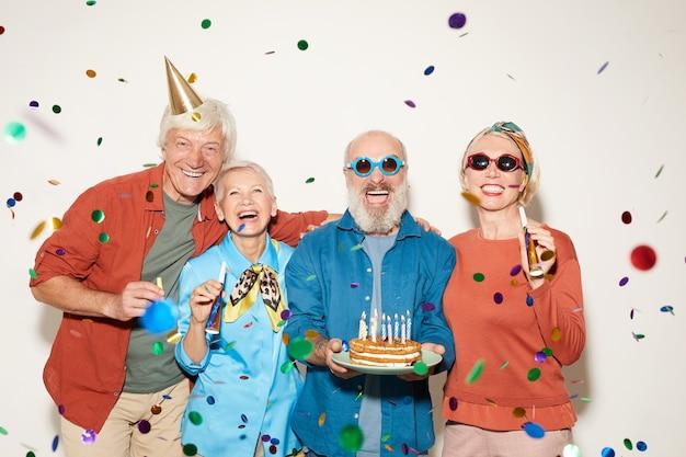 Portret van een groep senior mensen met een verjaardagstaart staan onder de confetti en glimlachen naar de camera tegen de witte achtergrond