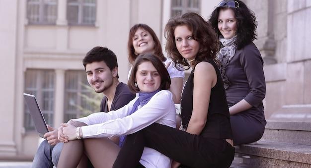 Portret van een groep studenten die voor de universiteit zitten