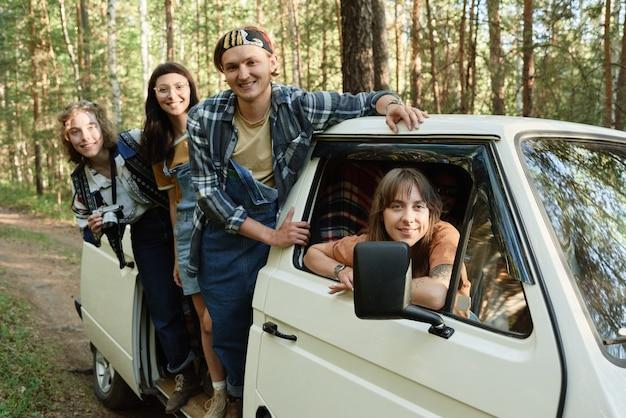 Portret van een groep toeristen die naar de camera lacht terwijl ze met de bus naar de wilde natuur reizen