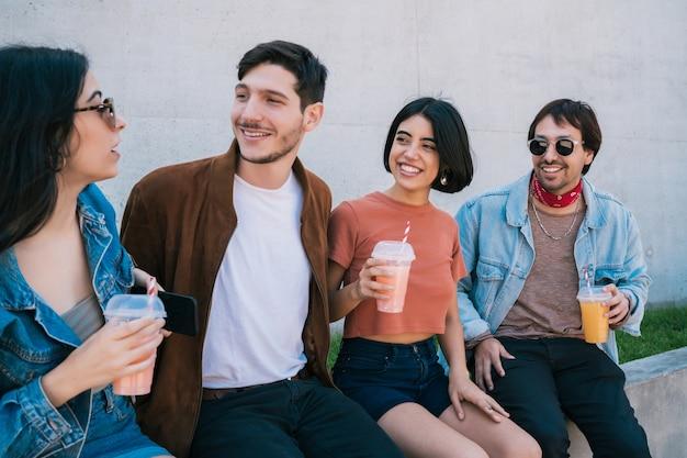 Portret van een groep vrienden die samen plezier hebben en genieten van een goede tijd terwijl ze vers vruchtensap drinken