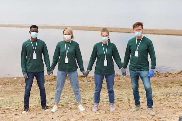 Portret van een groep vrijwilligers in beschermende maskers hand in hand terwijl ze buiten aan de oever van de rivier staan