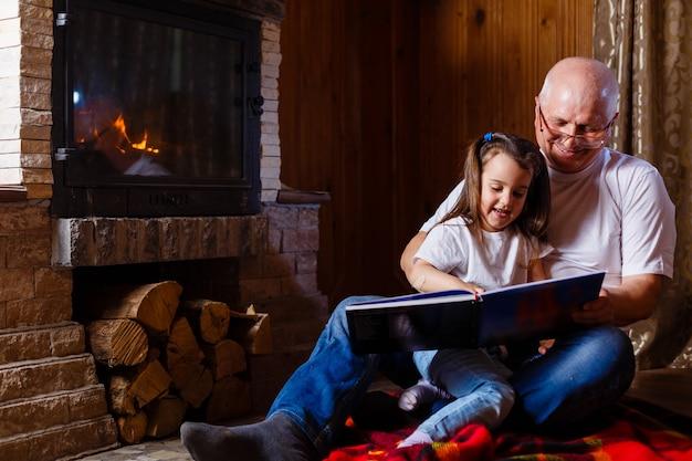 Portret van een grootvader in witte t-shirt die een verhaal leest aan zijn kleine, mooie kleindochter