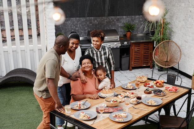 Portret van een grote afro-amerikaanse familie die liefhebbende grootmoeder viert tijdens het diner buiten kopieerruimte
