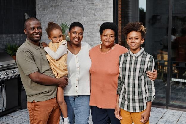 Portret van een grote afro-amerikaanse familie die naar de camera kijkt terwijl ze samen poseren op het buitenterras en...