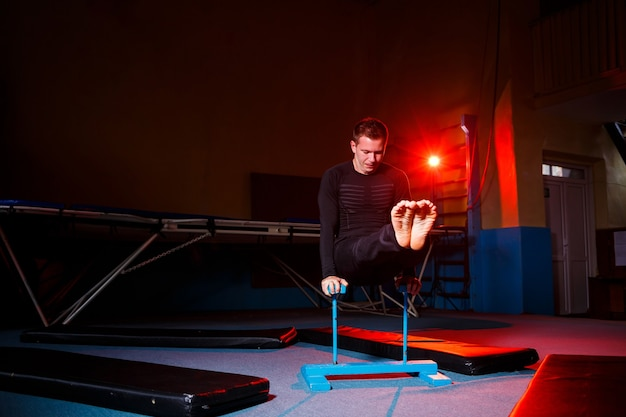 Portret van een gymnast in sportkleding, man die oefeningen doet op een paard in de sportschool