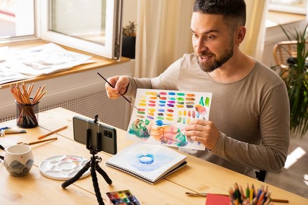 Portret van een halfvolwassen kunstenaar, een mannelijke donkerharige man die lacht en gelukkig maakt om online kunstles voor studenten te maken