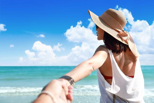 Portret van een hand van de paarholding op het strand met aardige blauwe hemel