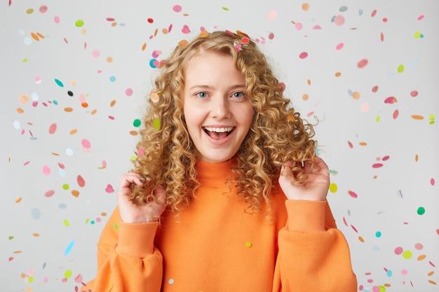 Portret van een heel gelukkig meisje in oranje trui raakt speelt met haar krullend haar, glimlachend naar vallende confetti