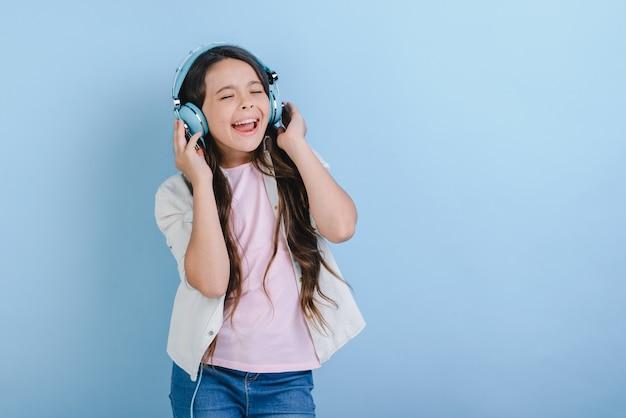 Portret van een heerlijk klein meisje met gesloten ogen in oortelefoons luisteren naar muziek en zingen