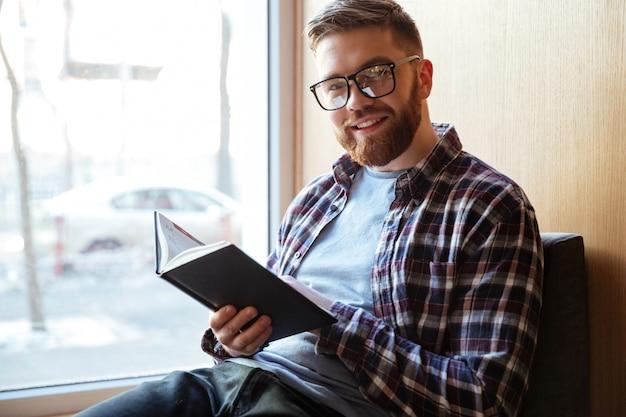 Portret van een het glimlachen gelukkig mannelijk boek van de studentenholding