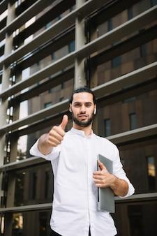 Portret van een het glimlachen laptop die van de zakenmanholding in hand duim toont ondertekent toont