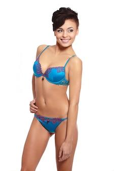 Portret van een hete jonge glimlachende vrouwelijke mannequin poseren in blauwe lingerie