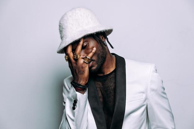 Portret van een hiphopmuziekmuzikant filmisch beeld van een man met witte kleren en juwelen