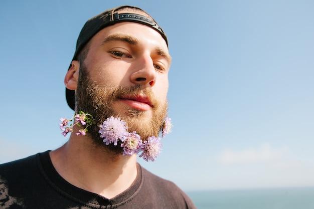 Portret van een hipster-man met de baard close-up en bloemen
