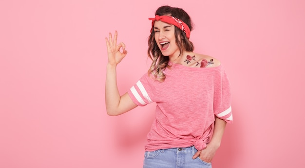Portret van een hipster meisje met tatoeage, geïsoleerd op roze achtergrond