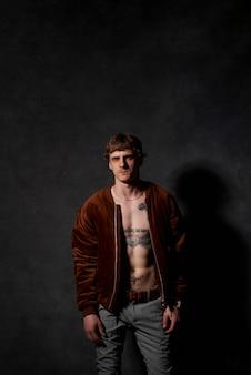 Portret van een hipster persoon met getatoeëerd lichaam in jas poses op donkere achtergrond