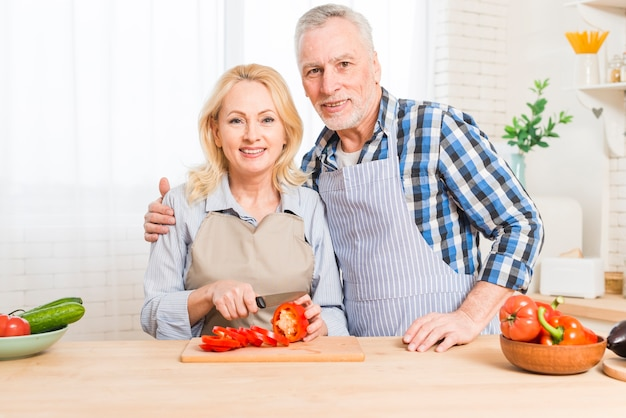 Portret van een hoger paar die camera bekijken die de groente voorbereiden