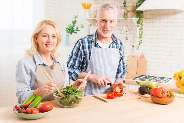 Portret van een hoger paar die de salade in de keuken voorbereiden