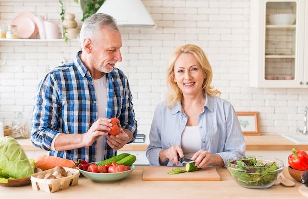 Portret van een hogere man die haar vrouw bekijkt die de groente in de moderne keuken snijdt