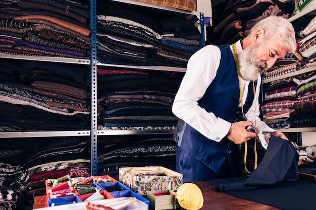 Portret van een hogere mannelijke kleermaker die een stuk van stof met schaar snijdt