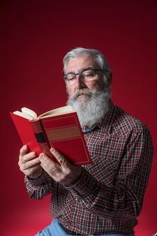 Portret van een hogere mens die het boek leest dat in hand tegen rode achtergrond houdt