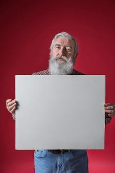 Portret van een hogere mens die leeg wit aanplakbiljet toont dat zich tegen rode achtergrond bevindt