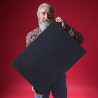 Portret van een hogere mens die leeg zwart aanplakbiljet toont dat zich tegen rode achtergrond bevindt